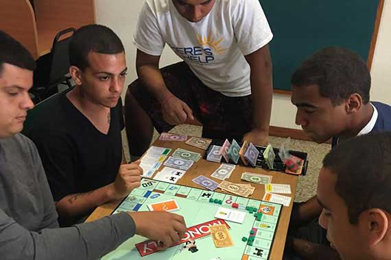 Photo of 5 young men gathered around a table playing monopoly