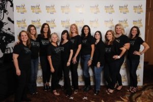 Eleven women posing in black shirts for a photo