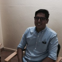 A young man sitting in a chair with glasses on and smiling for the photo
