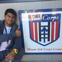 A young man posing for a photo next to a job corps banner