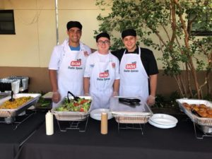 Three young men in aprons ready to serve food