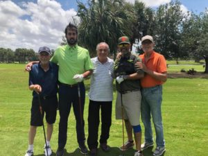 Five men striking a pose with a smile out on a golf course